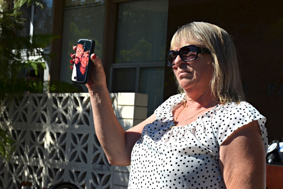 Bonnie Horne, Bobby Reynold's mother, holds up a photo of Bobby and his wife, Monica Reynolds.