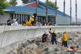 Redondo Beach firefighters rescue a man from the rocks along the sea wall at Redondo Beach Marina. Photo credit Nicole Mooradian.