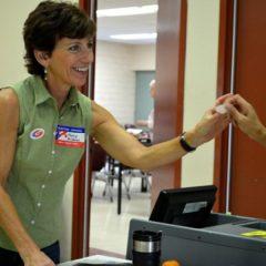 "Palos Verdes poll worker Nancy Wildman hands a voter an ""I voted"" sticker. Photo credit Nicole Mooradian."